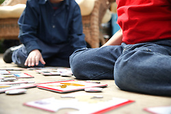 Two young boys playing with jigsaw puzzles,