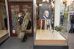 © Licensed to London News Pictures. 17/04/2021. Windsor, UK. A police officer carrying a gun bag waits to enter a shop displaying a picture of The Duke of Edinburgh in its window, in the town of Windsor, Berkshire, ahead of the funeral of Prince Philip, The Duke of York. Prince Philip, the Consort of the longest reigning English monarch in history, Queen Elizabeth II, died on 9 April 2021, two months before his 100th birthday. . Photo credit: Ben Cawthra/LNP