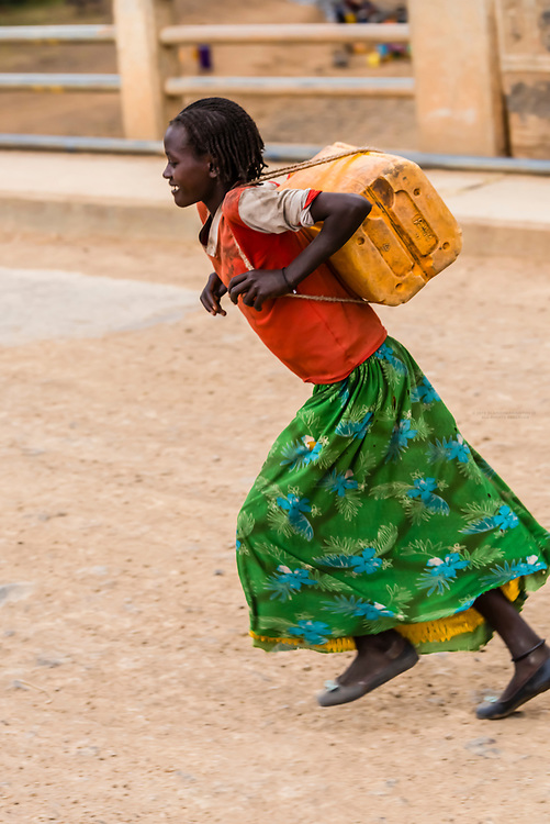 Konso tribe girl carrying a water container that she just filled at the Sagan River, outside Konso, Southern Nations Nationalities and People's Region, Ethiopia.