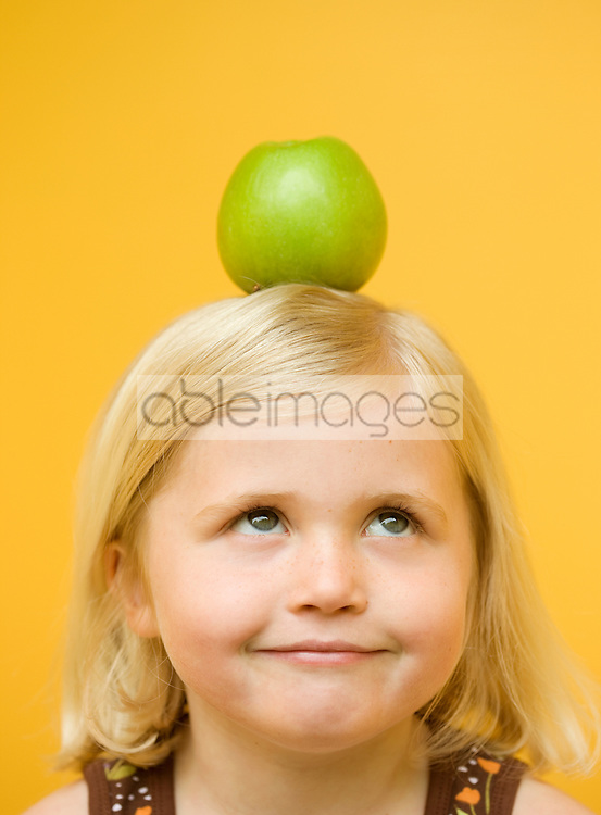 Close up of a young girl with a green apple on top of her head looking up
