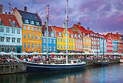 Nyhavn is a colourful 17th century waterfront, canal and popular entertainment district in Copenhagen, Denmark. Stretching from Kongens Nytorv to the harbourfront just south of the Royal Playhouse, it is lined by brightly coloured 17th and early 18th century townhouses and numerous bars, cafés and restaurants.