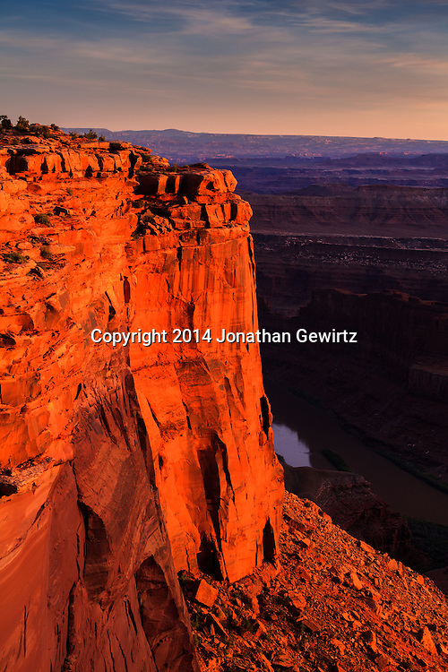 Warm light from the setting sun highlights Dead Horse Point over the Colorado River near Moab, Utah. WATERMARKS WILL NOT APPEAR ON PRINTS OR LICENSED IMAGES.<br /> <br /> Licensing: https://tandemstock.com/assets/71660318
