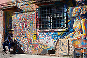 A man sitting with his head in his hands in front of a wall with street art grafitti on it, Vila Madalena neighbourhood, Sao Paulo, Brazil.