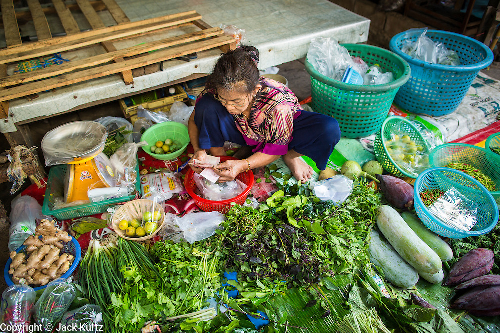 17 JANUARY 2013 - SAMUT SONGKHRAM, SAMUT SONGKHRAM, THAILAND: A vegetable vendor does business in the market in Samut Songkhram. Four trains each day make the round trip from Baan Laem, near Samut Sakhon, to Samut Songkhram, the train chugs through market eight times a day (coming and going). Each time market vendors pick up their merchandise and clear the track for the train, only to set up again when the train passes. The market on the train tracks has become a tourist attraction in this part of Thailand and many tourists stop to see the train on their way to or from the floating market in Damnoen Saduak.    PHOTO BY JACK KURTZ