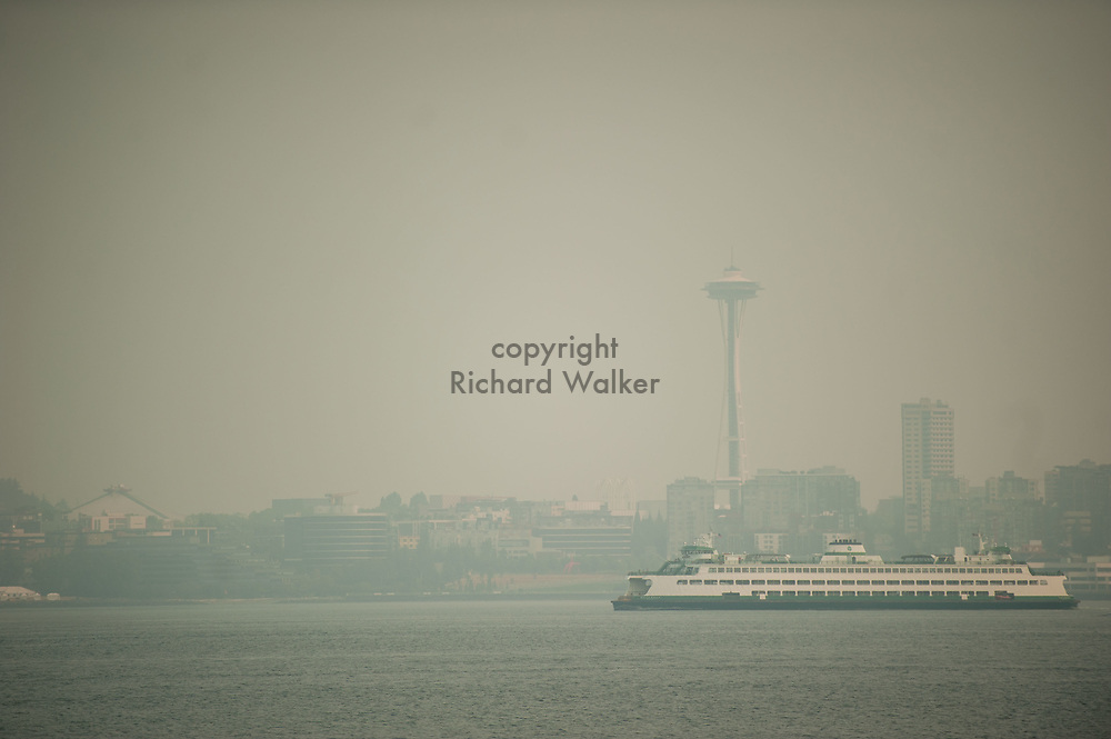 2018 AUGUST 20 - A Washington State Ferry sails in Elliott Bay with the Space Needle as a backdrop as smoke fills the skies of Seattle, WA, USA. Seen from near Don Armeni Boat Ramp in West Seattle. By Richard Walker
