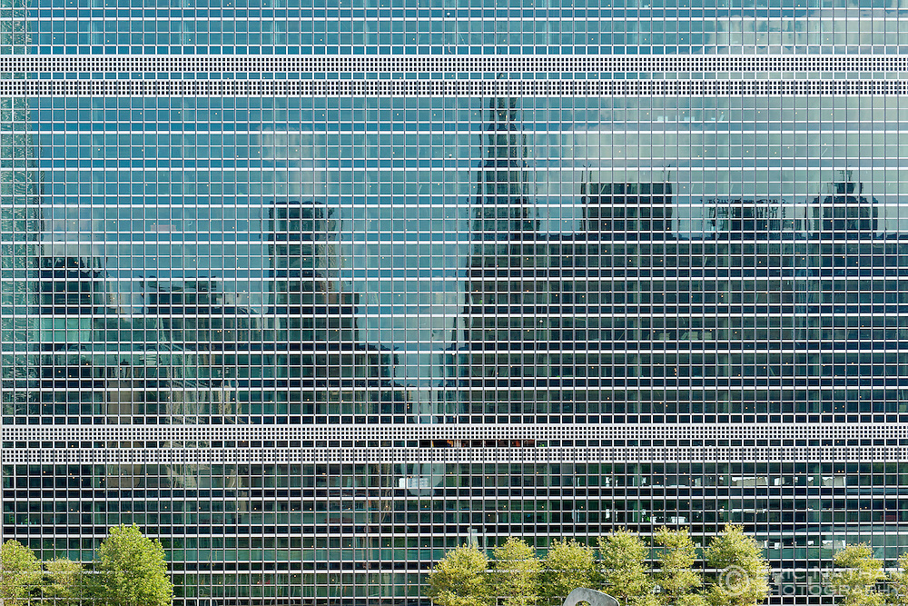 The Manhattan skyline reflected in the windows of the United Nations building in New York City, USA.