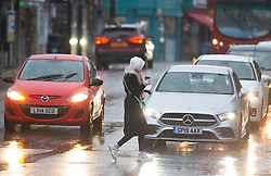 © Licensed to London News Pictures 03/01/2021.        Sidcup, UK. A woman gets wet crossing the road in Sidcup High Street. Heavy rain in Sidcup, South East London this Sunday afternoon as a weather warning has been issued for a -12C Arctic chill in the UK. Photo credit:Grant Falvey/LNP