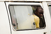 A man looks out of the window of a minibus as it drives through traffic in central Accra, Ghana on Tuesday June 16, 2009.