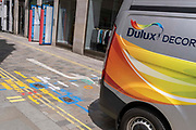 A van with the decorating and paint brand Dulux drives past multi-coloured aerosol-sprayed markings on the ground in a side-street off Long Acre near Covent Garden, are on 23rd June 2021, in Westminster, London, England.