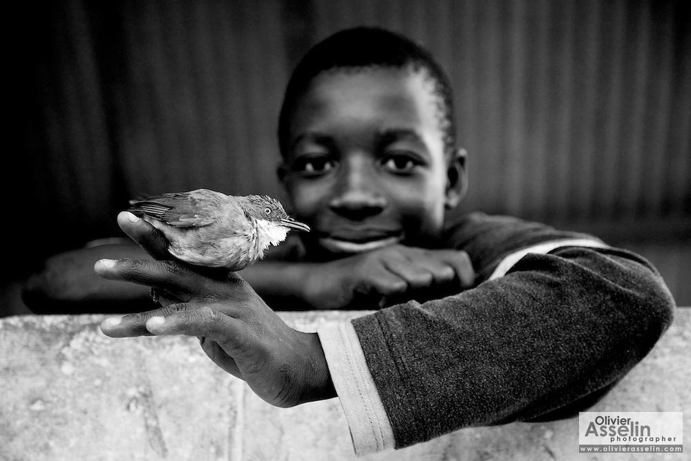 Boy holding bird, hunting, sling shot, cruelty