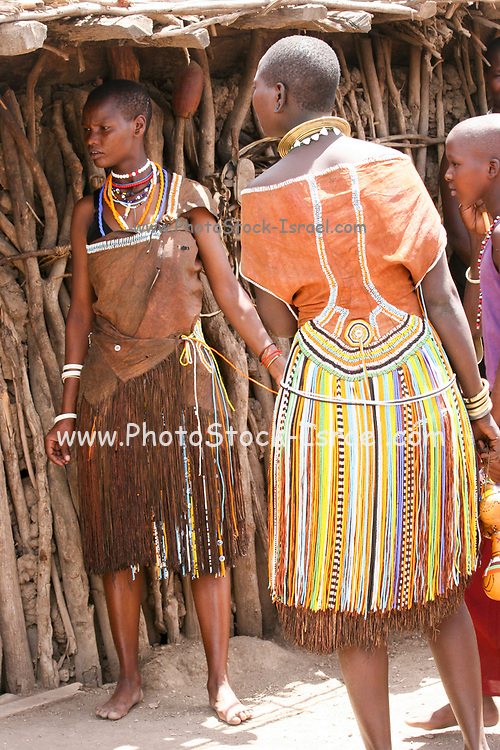 Datoga woman in traditional leather dress adorned with beads and brass bracelets