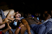 Migrants sleep at night on the deck of the German NGO migrant rescue ship Sea-Watch 3 as the ship makes its way to Trapani to disembark the 257 rescued migrants on board, off the coast of Sicily, Italy, August 7, 2021.  REUTERS/Darrin Zammit Lupi     TPX IMAGES OF THE DAY - RC220P93PI1Q