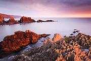 Evening light on the dramatic rock formations of Hartland Quay and Screda Point. A colourful sunset coastal scene in Devon, England, UK.