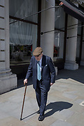 An elderly gentleman wearing a flat cap and a pinstripe suite walks slowly down Lower Regent Street with the aide of a walking stick, on 1st May, in London, England.