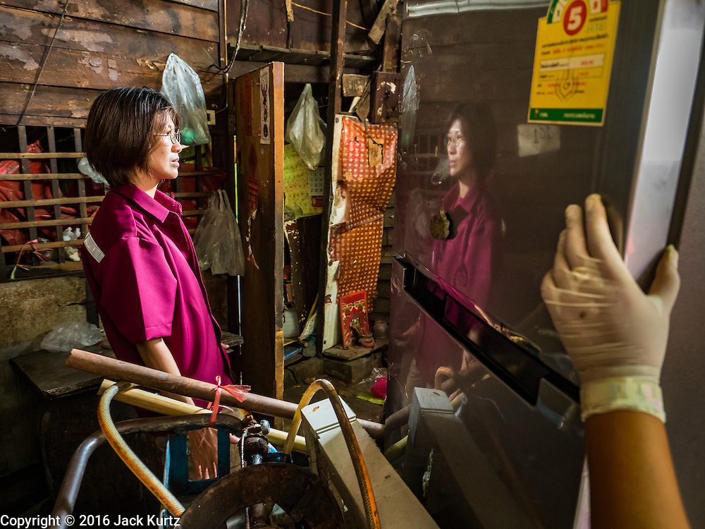 03 SEPTEMBER 2016 - BANGKOK, THAILAND: A Bangkok city worker is reflected in the refrigerator door of a Pom Mahakan resident during an operation to evict people from the Pom Mahakan community. Hundreds of people from the Pom Mahakan community and other communities in Bangkok barricaded themselves in the Pom Mahakan Fort to prevent Bangkok officials from tearing down the homes in the community Saturday. The city had issued eviction notices and said they would reclaim the land in the historic fort from the community. People prevented the city workers from getting into the fort. After negotiations with community leaders, Bangkok officials were allowed to tear down 12 homes that had either been abandoned or whose owners had agreed to move. The remaining 44 families who live in the fort have vowed to stay.      PHOTO BY JACK KURTZ