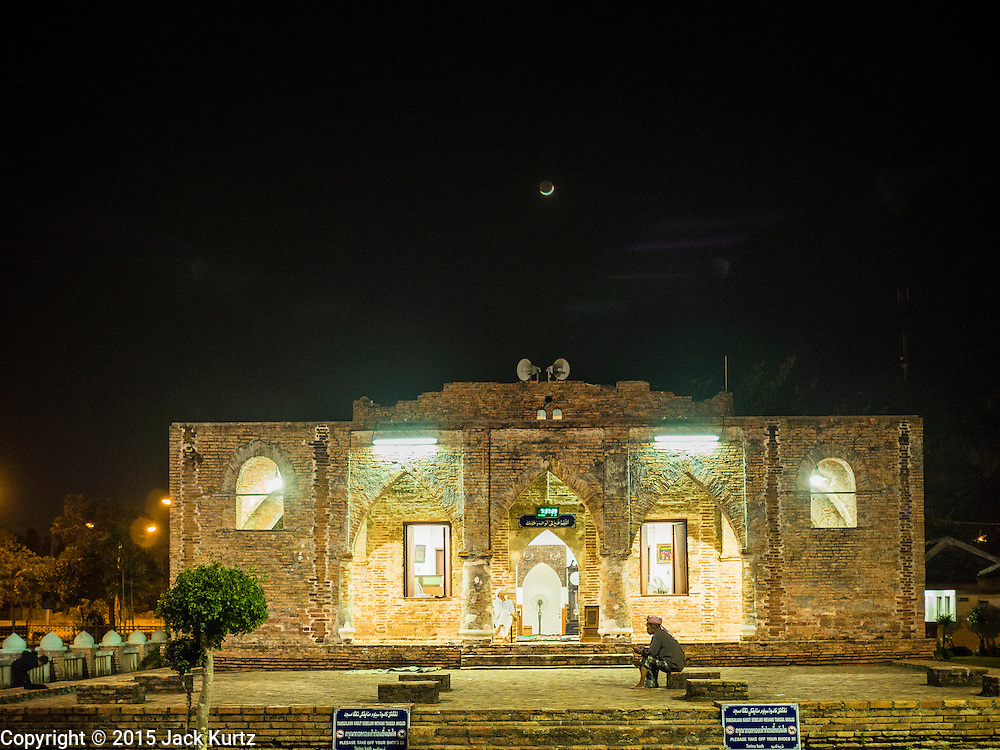 19 JUNE 2015 - PATTANI, PATTANI, THAILAND: The crescent moon behind Krue Se Mosque. Krue Se Mosque was started in 1583 but never completely finished. Ramadan is the ninth month of the Islamic calendar, and is observed by Muslims worldwide as a month of fasting to commemorate the first revelation of the Quran to Muhammad according to Islamic belief. This annual observance is regarded as one of the Five Pillars of Islam. Islam is the second largest religion in Thailand. Pattani, along with Narathiwat and Yala provinces, all on the Malaysian border, have a Muslim majority.             PHOTO BY JACK KURTZ