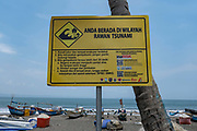 A large yellow tsunami warming signpost at the fishing village of Batu Karas on the 27th October 2019 in West Java in Indonesia.