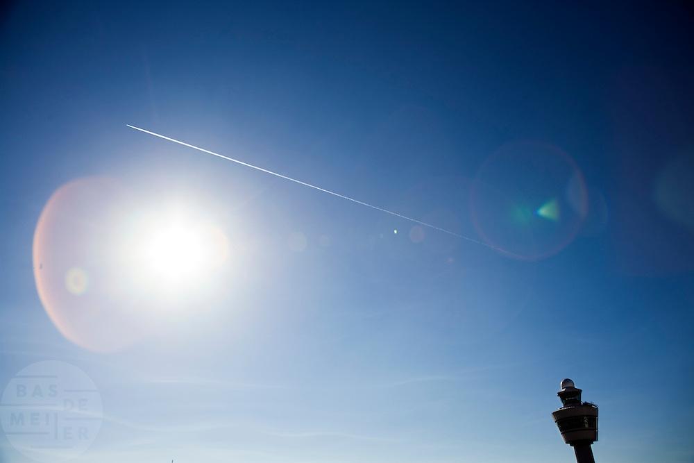 Een vliegtuig vliegt boven de verkeerstoren van luchthaven Schiphol<br /> <br /> A plane flying above the control tower of Schiphol Airport