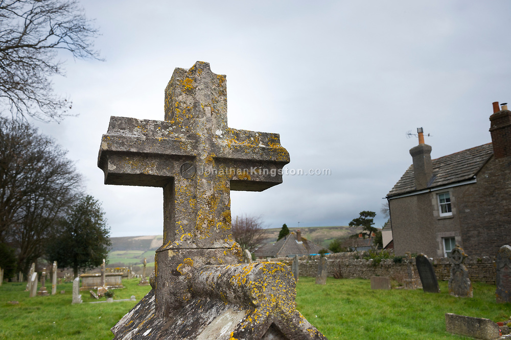 Stone lichen covered cross in a graveyard in Swanage, England.
