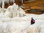 A girl sits on an ice formation at the Apostle Island Ice Caves, Makwike Bay, near Bayfield, Wisconsin, on a cold February day.