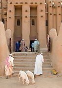 Men arrive at the Great Mosque of Djenné, the worlds largest mud built structure and UNESCO heritage site, in time for prayer. Djenné, Mali