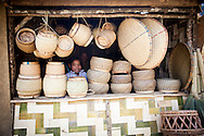 Face of young vendor through bamboo craft products in a shop in Ban Don Chai, Laos, Southeast Asia