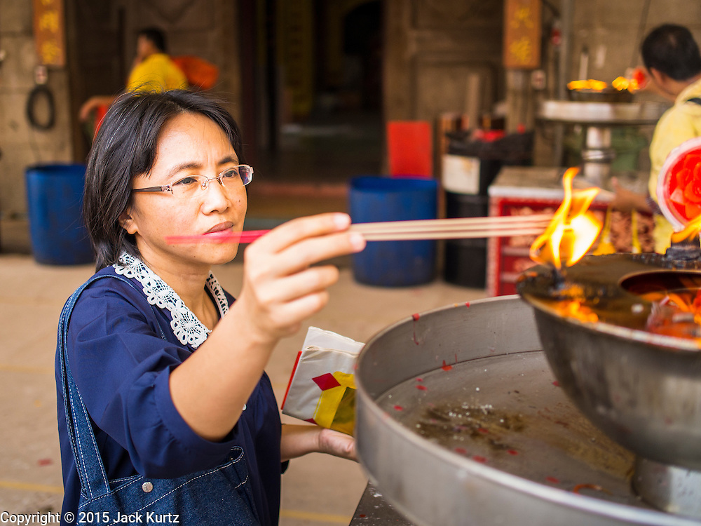 """17 FEBRUARY 2015 - BANGKOK, THAILAND:  People light candles and incense for Chinese New Year at Wat Mangkon Kamalawat, the largest and most important Chinese Buddhist temple in Bangkok. Chinese New Year is February 19 in 2015. It marks the beginning of the Year of Sheep. The Sheep is the eighth sign in Chinese astrology and the number """"8"""" is considered to be a very lucky number. It symbolizes wisdom, fortune and prosperity. Ethnic Chinese make up nearly 15% of the Thai population. Chinese New Year (also called Tet or Lunar New Year) is widely celebrated in Thailand, especially in urban areas like Bangkok, Chiang Mai and Hat Yai that have large Chinese populations.      PHOTO BY JACK KURTZ"""