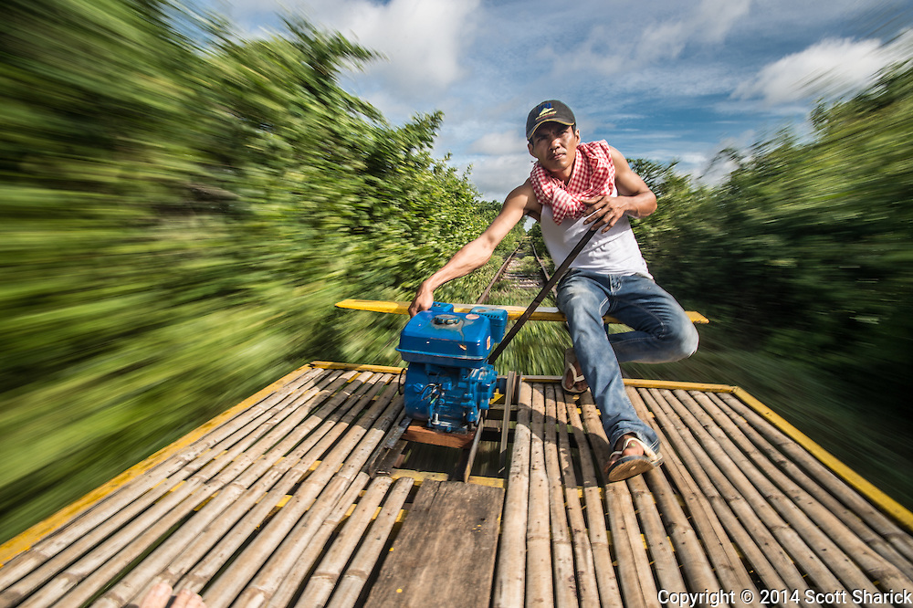 The Bamboo Train operates near Battambang, Cambodia. People and goods are transported on a single rail on a bamboo platform powered by a small engine.