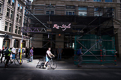 © London News Pictures. 04/09/2013. London, UK. A cyclist wearing sunglasses stops in a shaft of light caused by light reflecting off 20 Finchurch Street in the financial district of central London. Scaffolding (pictured) has been built to prevent the light overheating nearby businesses. The building, which has been named unofficially the 'Walkie Talkie' building because of its shape, intensifies the suns light and reflects it onto the street below. There have been reports of damage to vehicles and local shops caused by the heat of the reflected light. Photo credit: Ben Cawthra/LNP