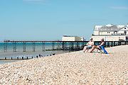 © Licensed to London News Pictures. 03/07/2014. Bognor Regis, UK. A couple relax in the sun near to the pier.  People enjoy the hot sunny weather at the seaside resort of Bognor Regis today 3rd July 2014. Forecasters are predicting it to be the hottest day of 2014 so far. Photo credit : Stephen Simpson/LNP