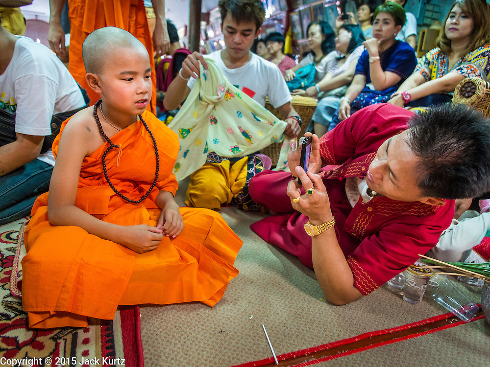 """06 APRIL 2015 - CHIANG MAI, CHIANG MAI, THAILAND: A boy just ordained as a Buddhist novice has his picture taken by a family member on the last day of the three day long Poi Song Long Festival in Chiang Mai. The Poi Sang Long Festival (also called Poy Sang Long) is an ordination ceremony for Tai (also and commonly called Shan, though they prefer Tai) boys in the Shan State of Myanmar (Burma) and in Shan communities in western Thailand. Most Tai boys go into the monastery as novice monks at some point between the ages of seven and fourteen. This year seven boys were ordained at the Poi Sang Long ceremony at Wat Pa Pao in Chiang Mai. Poy Song Long is Tai (Shan) for """"Festival of the Jewel (or Crystal) Sons.   PHOTO BY JACK KURTZ"""