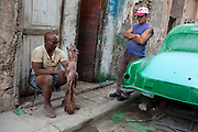 Cuban man making a sculpture of a ginat hand in the street, while his friend looks on leaning againist an ld car being re-sprayed. There are a lot of talented artists in Cuba, many working indepedently in their own time but with limited materials and outlets for their work.