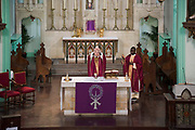 Father Michael Branch and Father Matthew Uche Ndibe delivers mass to parishioners via live-stream at on 27th March 2020 at St Peters Roman Catholic Church in Woolwich, London, United Kingdom. Following the governments advice on social distancing, the Catholic Church has suspended public worship until further notice to help slow the spread of the Coronavirus. Designed by Augustus Pugin in 1841-42 in the style of the Gothic Revival, St Peters RC,  is one of only three Pugin churches in London. In 1883 St Peter the Apostle Roman Catholic Church opened, the first to do so in London, following the Reformation.