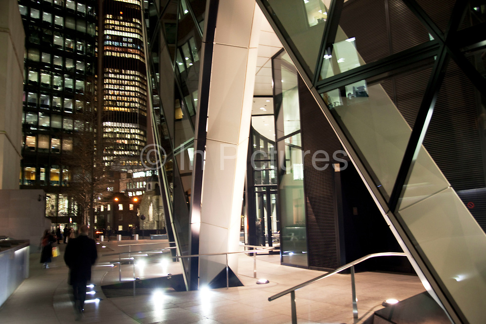 Night time scene in the City of London. 1 St Mary Axe, also knowns as The Gherkin in the City of London. This iconic building is one of the best loved buildings in London with it's distinctive bullet like shape and twisted glass exterior.