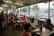 Drinking beer in an open-air bar during a monsoon, Cubatão