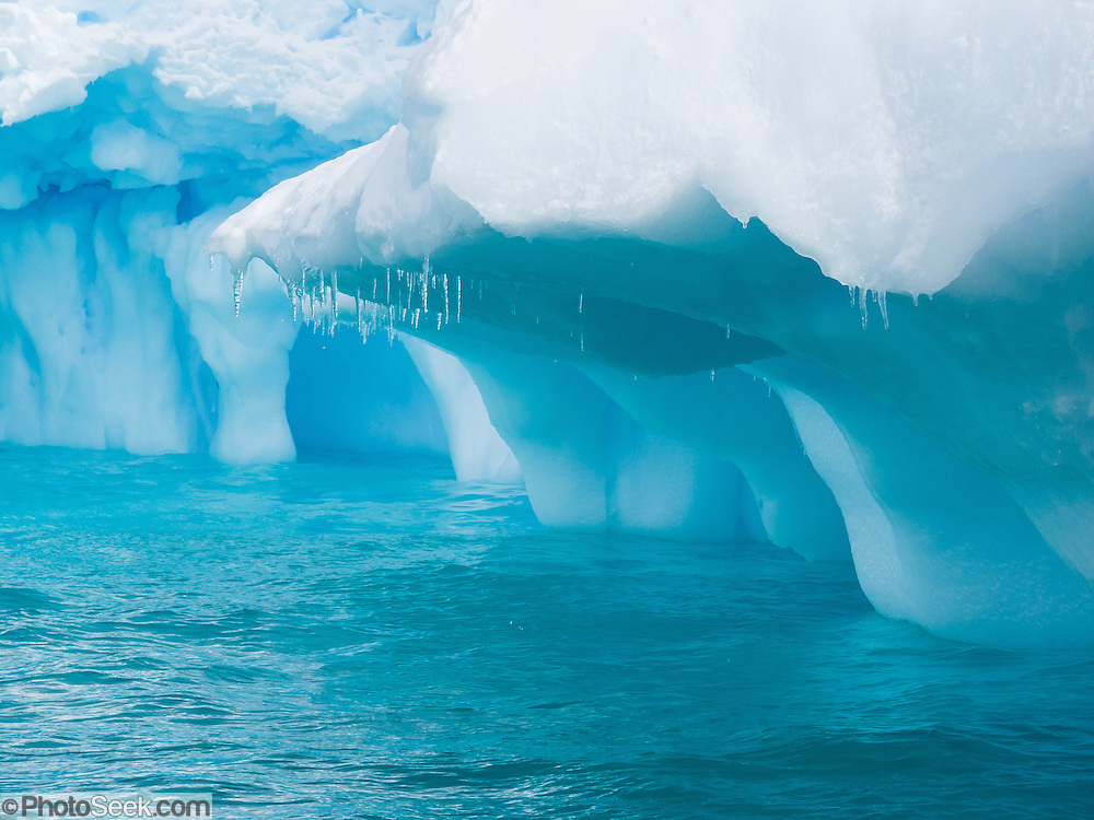 icicles drip from an icy overhang which was carved by waves undercutting an iceberg, in the Southern Ocean offshore from Graham Land, the north part of the Antarctic Peninsula, Antarctica.