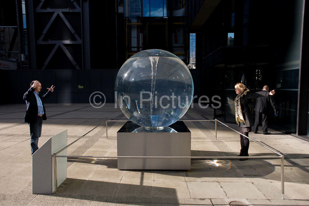 Distortion seen through Petroc Sesti's art instillation called Time Fold in Great Helen's Square, in the City of London. A coupe look at each other's magnified heads and outstretched arms through the optics of this art prism. Petroc Sesti is a London based British artist and Time Fold bends light like a prism, hypnotising the viewer by reflecting on its ever-changing spiral motion.