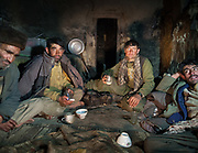 Wakhi men having diner of salty tea and bread, in a winter shepherd house. Chirog Don shepherd place.<br /> <br /> Trekking up the Wakhan frozen river, the only way up to reach the high altitude Little Pamir plateau, home of the Afghan Kyrgyz community.