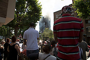 TV and other media reporting from near to a blaze at Grenfell Tower near Notting Hill on 14th June 2017 in West London, United Kingdom. The huge fire engulfed the tower block, trapping many people in their homes. A number of fatalities are reported. The block of flats in the Borough of Kensington and Chelsea, billowed large plumes of smoke way above the capital after the blaze broke out in the early hours of Wednesday morning. Londoners came out on the streets to help, offer food and water, support and assistance to those who had lost their homes or didn't know the whereabouts of their friends and family.