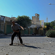 A rebel fighter shoots at pro-Gaddafi snippers during the third day of street-to-street battle for control of the strategically coastal city of Zawiya.