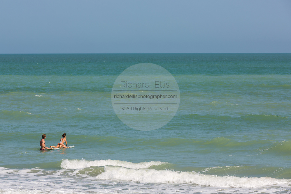 A young couple surfs along Folly Beach on a spring day May 12, 2014 in Charleston, SC.
