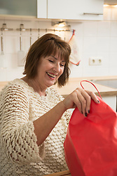 Senior woman looking into shopping bag and smiling in the kitchen, Munich, Bavaria, Germany