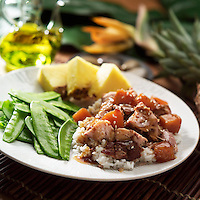 Hawaiian haystack made with pork and rice with snap peas and pineapple of the side.