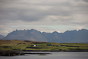 Across the calm waters of a Scottish bay, isolated houses and crofts sit before the dramatic Cuillin Mountains that rise up in the distance on the Isle of Skye, Scotland. Sunlight from unusually fine weather spreads across this beautiful landscape seen from the road to Dunvegan, near the hamlet of Harlosh. Farming practices have changed irreversably in a generation and many southerners have English accents rather than that of native Scots islanders as city dwellers from the far south seek an alternative to urban lifestyles. The weather can have adverse effects on those unprepared for such wild conditions, especially during harsh winters when violent storms batter these Atlantic coasts. But old crofts have been converted to bed and breakfast homes, catering for tourist visitors who adore this form of idyllic escapism.