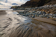 A stream braids sand into patterns on Chapman Beach before flowing into the Pacific Ocean. Cannon Beach city, Oregon coast, USA.
