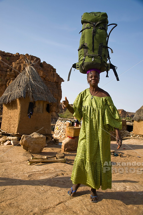 Dogon country, Mali, West Africa - A Dogon woman balances a travellers backpack on her head for a photo op. A traditional dogon grainery is in the background.