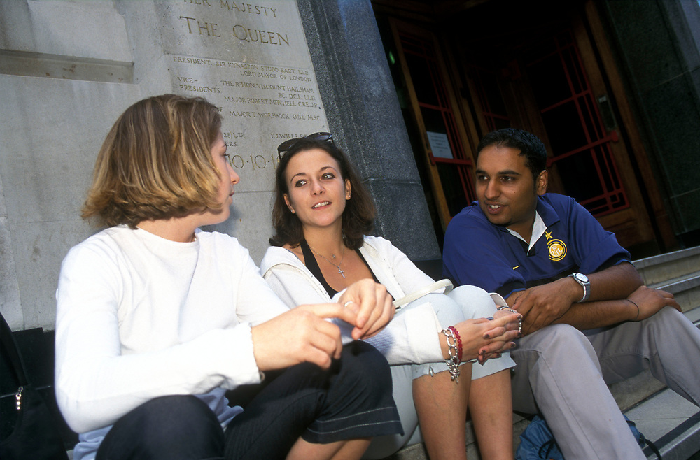 Group of students at Further Education College chatting on steps,