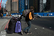 Street scene of a busker puling his belongings behind him in the City of London, England, United Kingdom. (photo by Mike Kemp/In Pictures via Getty Images)