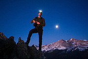 Obadiah Reid on the summit of Twin Sisters Mountain at dawn in Rocky Mountain National Park, Colorado. The moon is setting over Longs Peak behind him.