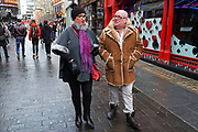 Street scene in Soho with a man with matching facial hair and sheepskin coat trim in London, England, United Kingdom.
